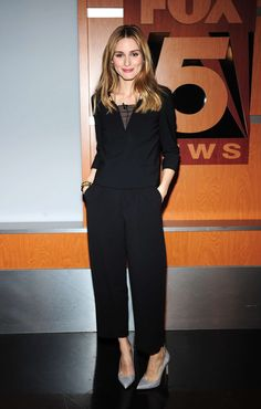 Olivia Palermo in a black top, matching black pants and gray snakeskin pumps for her appearance on the Good Day New York TV show.