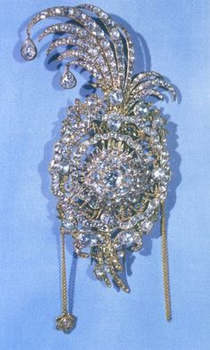 """This aigrette is made of solid gold and studded with diamonds. Around the center sunburst, the words """"Al-Sultan Ibn-Sultan Fath-Ali Shah Qajar"""" appear in rubies. The word Qajar is misspelled, suggesting that the jeweller who designed the piece did not have an adequate grasp of Farsi, the Persian language. Thus, it is believed that this is one of three aigrettes presented by Russia's Czar Alexander I to Fathali Shah in 1817."""