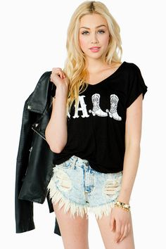 Get 'er done! A fun relaxed fit top featuring a 'Y'all' front graphic and a round neck. Short sleeves. Finished hem. Knit. Pair it with daisy dukes and cowboy boots for a rockin' look!