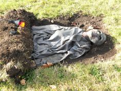 Unearthed zombie corpse.  I love this idea for a cemetery! I WANT TO DECORATE MY HOUSE FOR A HALLOWEEN PARTY LIKE THIS!!