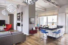 <p>Salon z kuchnią urządzony jest w bieli i szarości. Kolorowe dodatki ożywiają monochromatyczne wnętrza. Aranżacja jest nowoczesna i elegancka, urządzona pod potrzeby mężczyzny. Prezentujemy świetnie urządzone męskie mieszkanie.</p>