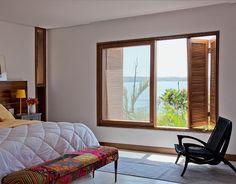 Ampla – 2,40 x 1,70 m – e com venezianas do tipo camarão, a janela escancara a paisagem e deixa o sol entrar no quarto da suíte principal. O rodapé leva a mesma madeira, cumaru. Poltrona da Clami Design.