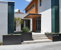 The exterior combines gray Lueders Limestone with white stucco from LaHabra and vertical Douglas fir siding. The designs of the guest house (to the left of the main house) and carport (to the right) follow the downward slope of the lot.