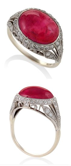 An Art Deco platinum ring with ruby and diamonds 1920s. The ring centers on an oval shape cabochon ruby with an approximatel weight of 7.25 carats. It has 48 single-cut diamonds with an approximate total weight of .24 carat that decorate a pierced and milligrain platinum setting with a foliate motif. #ArtDeco #ring
