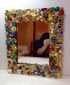 Mirror with jewel embellished frame. This handmade frame is decorated with vintage jewelry and has a very eclectic style. Jewelry is gold, silver, red, green and blue. If youre looking for a one of the kind statement piece, this is it! Dimensions are 15 high x 13 wide x 1 thick. Im constantly amazed by the beautiful old costume jewelry I find thats been hidden away for years. I love saving and preserving its beauty and the history of past generations.