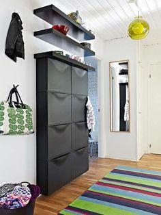 deco couloir avec plafond revêtu de bois peint en blanc, grand meuble rangement IKEA en noir, deux étagères noires, tapis en rayures horizontales en rouge, vert, bleu marine et bleu pastel
