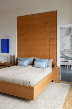 In the master bedroom, the custom-made bed is covered in a cotton by Rogers & Goffigon, the pillows are made of Glant fabrics, the painting is by Jason Martin, and the jute rug is by Holland & Sherry.   - ELLEDecor.com