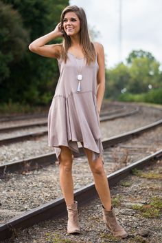 """Can you believe the cut of this fun tunic!? The multi-length hem creates such stunning movement and looks positively delicate in taupe! Wear it over leggings or your bare beauties for a fall look that is gorgeous either way!   Material has no amount of stretch. Adjustable straps.  Miranda is wearing the small.   Sizes fit:  Small- 0-4; Medium- 6; Large- 8   Length from shoulder to hem: S- 35""""; M- 36""""; L- 37""""."""
