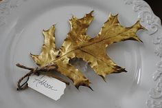 Gilded leaf place cards....I would use silk or metal leaves
