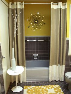 I love the double shower curtains hanging from the ceiling like that. Makes the bathroom look bigger!