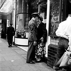 Bert Hardy: A couple talking on a street in Piccadilly, London. Date unknown.