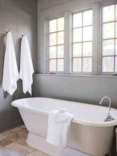Cottage bathroom features walls clad in gray shiplap framing windows over an oval freestanding tub paired with a gooseneck tub filler facing his and her towel hooks.
