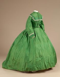 """Description: Apple green silk dress; gathered waist and high neckline; 10 cloth buttons down front and wire support stitched into the lining above the waist; skirt has train on back which extends 13"""" below hemline of dress; lining of brown linen; heavier linen sewn on the bottom 8"""" of dress' piped seams and decorative lace and silk trim on bodice and sleeves  Category: Personal Artifacts  Date Made: ca. 1850-1860  Material: silk  Litchfield Historical Society"""