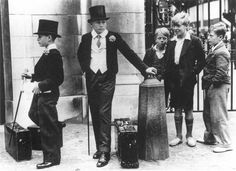 Class differences. Britain, 1937 - 30captivating historical photographs that you need tosee (kids, children, waiting, school, clothes, black and white, canes, top hats, coats, lower class, higher, hierarchy, gate, outside, day time, no color old photo, photograph, 30s, 1930s)