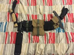 My Bushcraft Belt. From left to right: Leather Work Gloves, Becker Knife 9, Fire Kit (Black), Emergency Survival Kit (Tan), Folding Dump Pouch (Condor Outdoor), Cell Pouch (One Tigris), Knife: The Defender (Tops Knives), Lighter, & Flashlight. YouTube video coming soon.