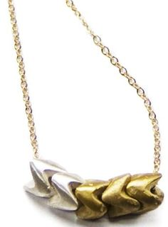 The Notch Necklace features three brass and two silver metal beads that nestle together on a rope chain. $130