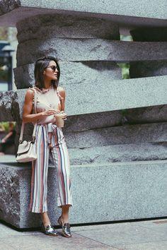 Camila Coelho during NYFW on her way to watch Akris fashion show wearing colorful striped pantacourt, a blush sleeveless with ruffles top, and metallic oxfords. A caminho do show de Akris usando pantacourt listrada, uma regata com babados e oxfords metalizados.