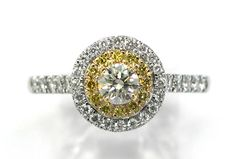 Ladies 14kt white and yellow gold diamond ring. Ring has 1 round cut diamond in center. Also set in mounting are 12 round cut natural yellow diamonds and 32 brilliant round cut white diamonds. A total of approximately .64ct total weight.