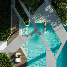 A canopy of concrete frames appears to slice up this rooftop swimming pool in Bangkok
