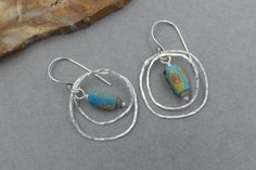 SALE! To celebrate the New Year, use coupon code: HAPPY2017 to save 17% off everything for the month of January. New items added regularly.  These earrings feature two rustic, organic, hammered, textured Fine Silver hoops along with colourful baby blue beads with lots of pitting and patina made from Ancient roman Glass hanging from Sterling Silver ear wires.  They hang approximately 1 3/4 long.
