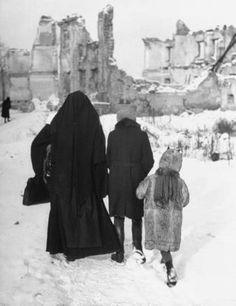 Sister Rafaela of the Benedictine Order trudging with children through the ruins of the old city. Photograph by Tony Linck. Poland, 1947.