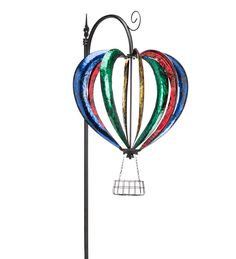Our Hot Air Balloon Wind Spinner is ready for summer! Blue, red, green and yellow metal arcs form the body of the balloon and spin 'round and 'round when the breeze blows. Below the balloon, a small metal basket sits ready to hold a small plant or perhaps some figurines that you think might enjoy a float through the skies.