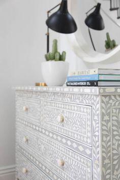 An Aiden Global Bazaar Grey and Cream Bone Inlay 4 Drawer Dresser is topped with stacked books, a potted cactus, and a black and gold task lamp placed beneath a round white convex mirror. Furniture Makeover, Diy Furniture, Passion Deco, 4 Drawer Dresser, Drawers, Ideias Diy, Furniture Restoration, My New Room, Painted Furniture