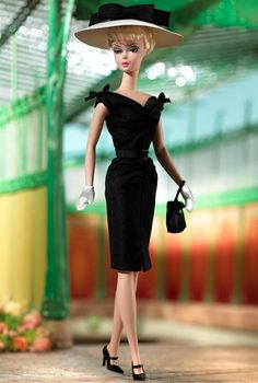 Completely proper but never prim, City Smart™ Barbie® doll models an air of cool refinement. Sleek sophistication is evident in her black shantung sheath dress worn with classic black and white accessories.
