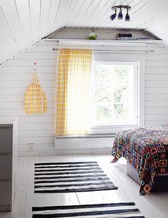 Toinen yläkerran makuuhuoneista on värikäs. Mummolassa kuuluu olla mummonruuduista virkattu päiväpeite. Verhot ovat suosikkikuosi Sienaa.
