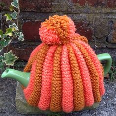 Brown and orange pleated pom pom tea cosy