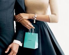 Tiffany's Iconic blue bag branding against conservative, semi-formal, excessively deep, mysterious pleats. You can't tell which of the three objects is supposed to be the arm candy.
