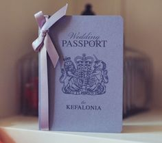 Destination wedding passport invitation. Soft dove grey cover with pretty inner styled pages tied up with a satin bow