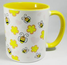 Bees Amongst the Flowers Mug with yellow glazed handle and inner. Cheerful cartoon bees on a bright yellow mug. A high quality ceramic mug with a yellow glazed handle and inner. Dishwasher proof. Height is 9.5cm, diameter 8.2cm, with a capacity of 310 ml . From the Series 9 Nature Range by Half a Donkey Ltd. www.halfadonkey.co.uk
