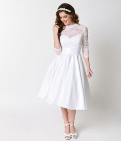 A vintage vision fresh from Heart of Haute and Bettie Page Bridal, the white lace and satin 1950s Colette wedding dress is a retro design that is truly heart stopping. A scalloped sheer high lace neck is fitted and met with sheer three-quarter sleeves, wi