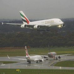 Emirates Airbus A380-842 landing while a Virgin Australia Boeing 737-800 and Jetstar Pacific Airbus A320-200 hold position