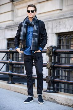 Men's Black Sunglasses, Navy Plaid Scarf, Blue Longsleeve Shirt, Black Bomber Jacket, and Navy Slip-on Sneakers