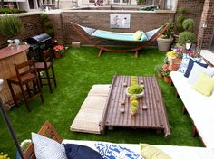 HGTV's Great Rooms transformed this enclosed patio into a bonafide backyard complete with astroturf, potted plants and topiaries. A tropical outdoor bar cozies up to the grill, while seating comes in many shapes and sizes: woven floor cushions, a hammock or an extra-long outdoor sectional.