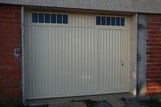 Portal de corredera motorizado, con puerta peatonal incorporada. Material: hierro galvanizado, pintado en color marfil.