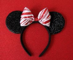 these christmas santa claus ears are glistening with red sequins with an underlay of red satin a black satin bow and feather trim to create t