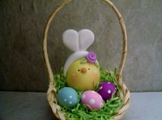 A little chick has donned a pair of bunny ears and sits tucked in a basket. She has with her a trio of Easter eggs!  This is an original design thats been handcrafted from polymer clay. The basket stands approximately 4 tall. All parts have been secured with liquid polymer for increased strength.   Not a toy...not suitable for young children.