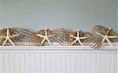 """Beach decor starfish garland using cool BROWN nautical decor netting and large 4-6"""" real white starfish. A nice long 10 foot size too!  Coastal decor wedding or Christmas garland, totally wired throughout so you can shape it however you'd like around anything.  This cool nautical netting starfish garland would make a great addition to your Christmas tree, strung on a mantle, on the deck or patio, or on a curtain rod as part of a window treatment.  Free ends.   Measures 10 feet long."""