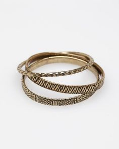 Collection of three various sized brass metal bangles with etched abstract designs from Dream Collective.
