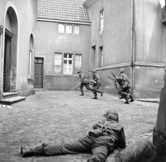 """British infantrymen of 3rd Division (nicknamed """"Monty's Iron Sides"""") clear out pockets of German snipers in a German town just across the Dutch-German border. Lingen, Lower Saxony, Germany. 7 April 1945"""