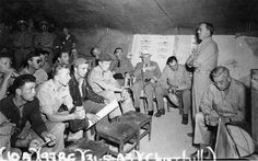 Inspecting North African bases, Winston Churchill attends a USAAF 414th Bombardment Squadron briefing at Chateau-dun-du-Rhumel Airfield, Tunsia, 31 May 1943. Alan Brooke, Chief of the Imperial Staff, is seated to Churchill's right.