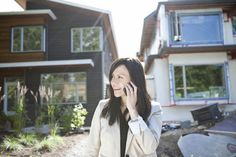 Mixed race real estate agent standing near house talking on cell phone