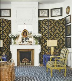 In this version of his living room, Castillo's mastery at mixing patterns can be admired once again. The ornate gold and navy trellis patterned screen contrasts pops against the white fireplace and walls. The plaid chair fabric works surprisingly well with the intricately patterned blue and white rug. Image courtesy Casas & Gente Magazine, Spain.