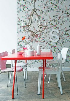 this delicately feminine yet modern dining room, with the bright red table, sculptural chandelier and wallpaper!