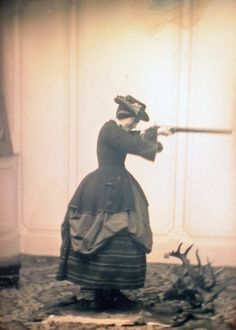 1850s/1860s  Woman hunter. Skirt tucked up over a striped underskirt. Wearing either a small hoop or a LOT of petticoats underneath.