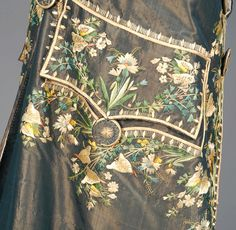 LOT 505 GENTS FRENCH EMBROIDERED SILK FORMAL COAT, 1750-1775 Blue changeant silk having stand collar, oversized pockets concealed beneath flap, pleated back, all DECORATED in polychrome silk floral, embroidered buttons throughout. Ch-36, Sh-14, Slv-26, L-43. (Relined, embroidery losses-mostly around collar, buttons and front opening, faint spot and fade marks on back) very good. MMA. $2,040