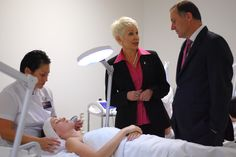 Principal Catherine Wouters speaks with Prime Minister John Key while Ena performs a facial treatment.